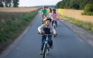 Familie fährt auf Fahrrädern auf einer Straße durch Felder