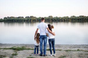 Eine Familie steht am Rheinufer und schaut aufs Wasser