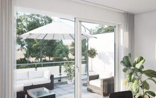 Blick durch eine Fensterfront auf eine Terrasse im Sonnenlicht