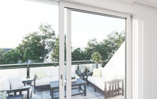 Blick durch eine Fensterfront auf einen großen Balkon mit Polstermöbeln