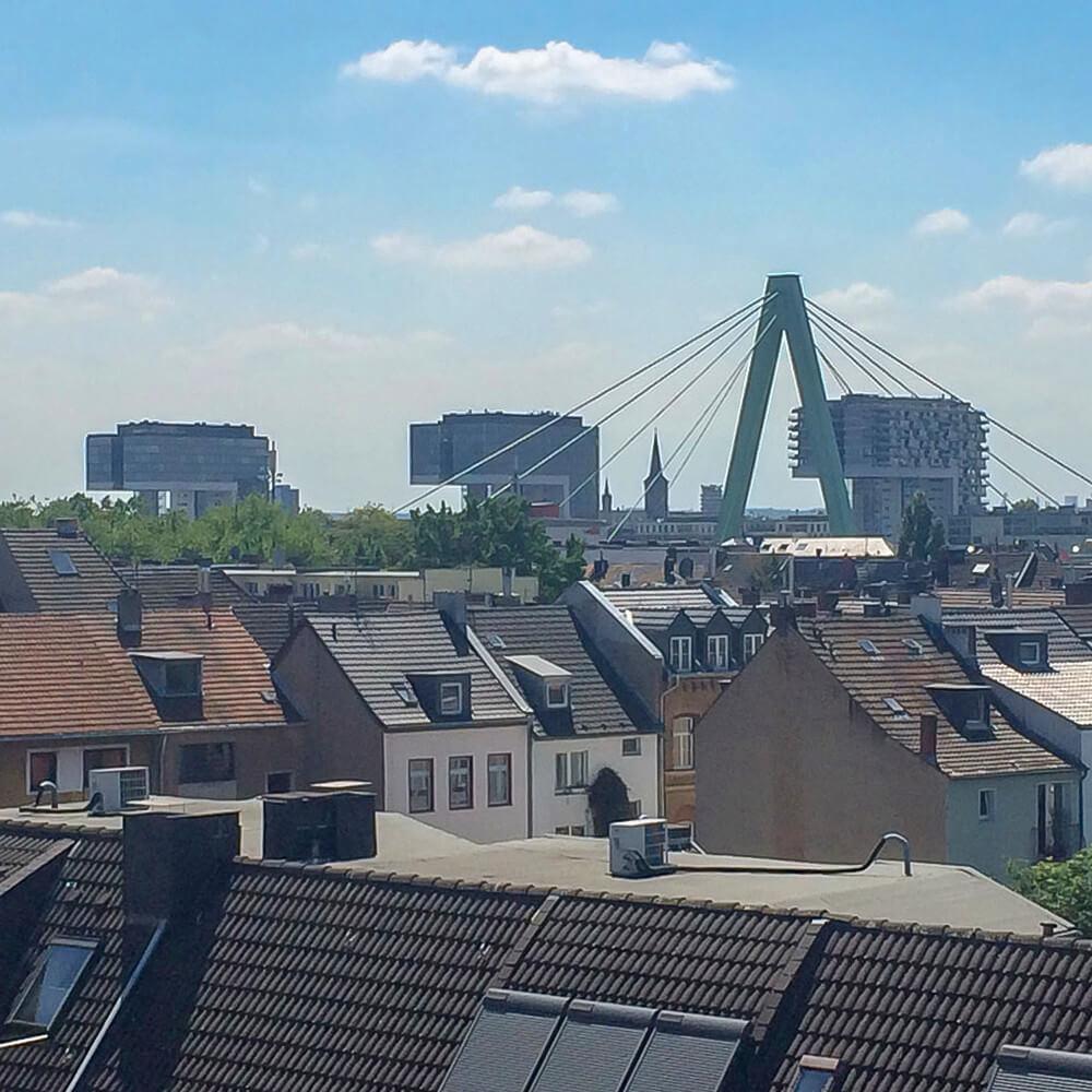Aussicht über Hausdächer mit Blick auf Kölner Kranhäuser