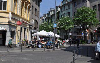 Mehrere Menschen sitzen vor einem Restaurant unter Sonnenschirmen