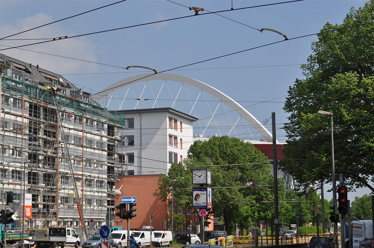 Häuserfassaden mit dem Dach der Lanxess-Arena im Hintergrund