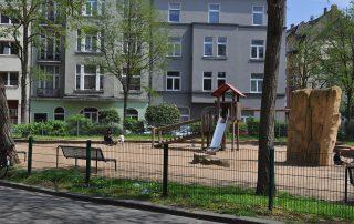 Ein Spielplatz mit mehrstöckigen Häusern im Hintergrund