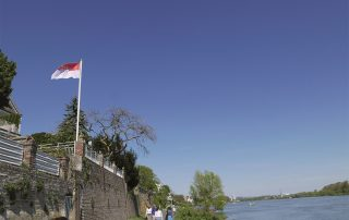 Gebäude mit Köln-Fahne am Ufer des Rheins